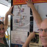 Eine Buchhändlerin hängt mit Ernst Lorenzen ein Plakat auf