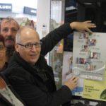 von li.: Bärbel Kitzing, Hermann Fickenfrers und Ernst Lorenzen hängen ein Plakat an einem Buchladen auf | Foto: Achim Scholz