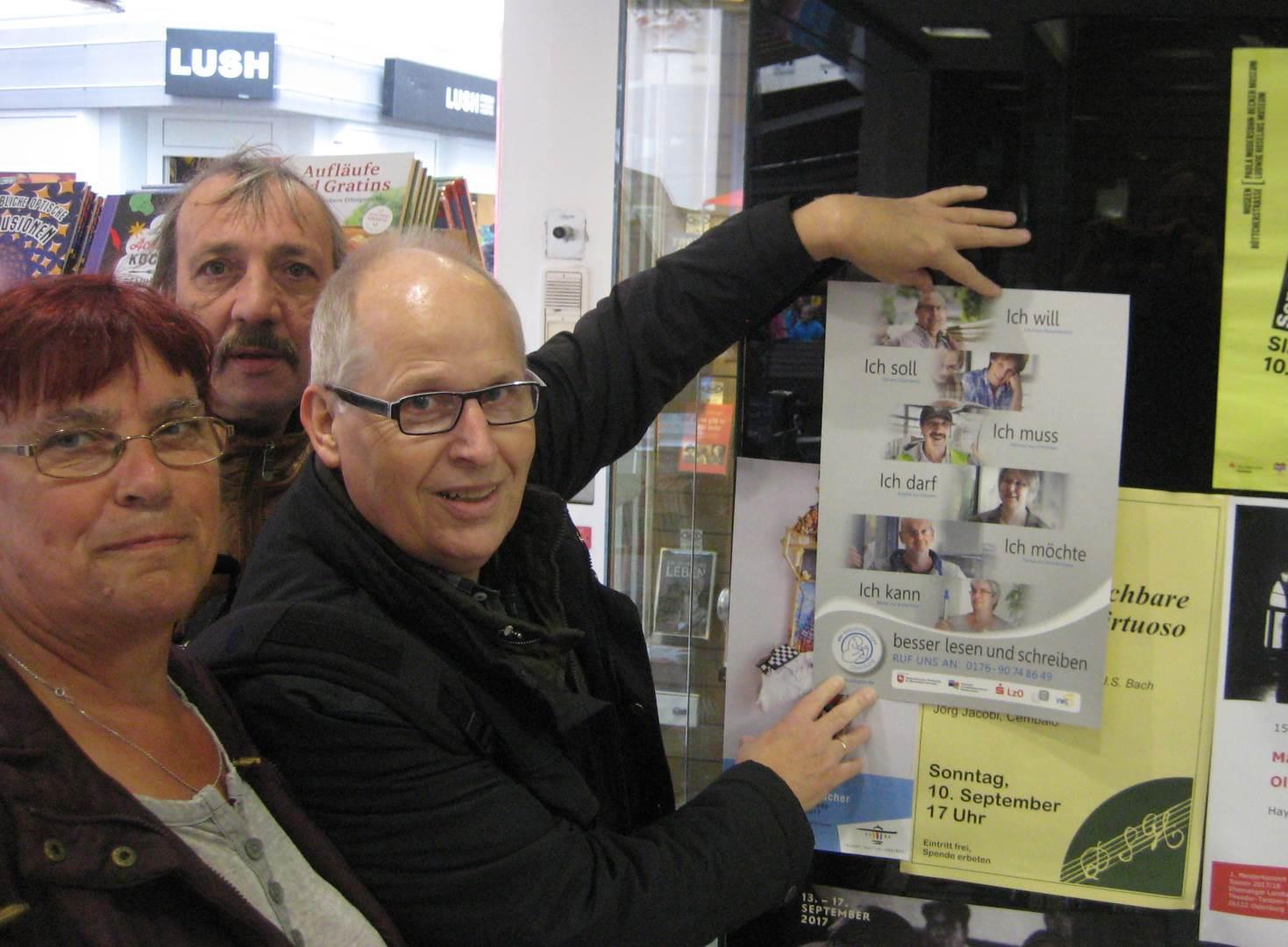 von li.: Bärbel Kitzing, Hermann Fickenfrers und Ernst Lorenzen hängen ein Plakat an einem Buchladen auf   Foto: Achim Scholz