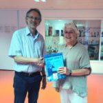 Gerrie Overwell von Prago übergibt Achim Scholz als Bezugsperson der Gästegruppe Gastgeschenke