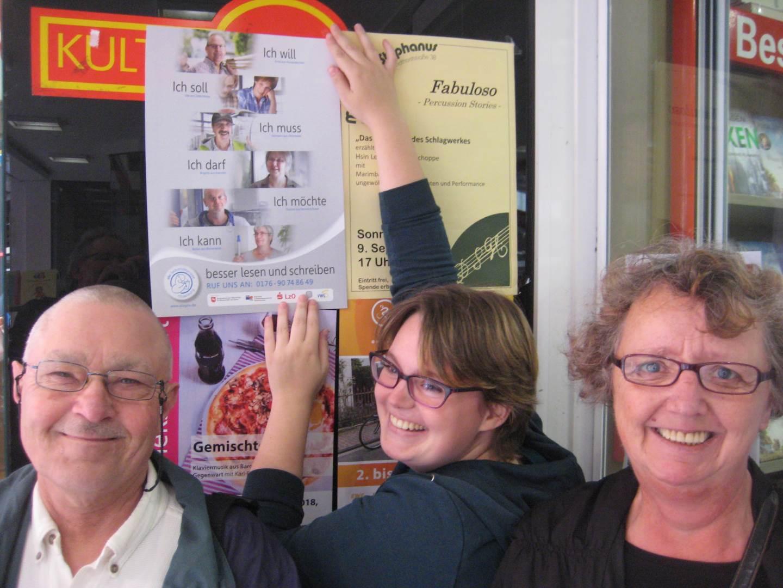 Klaus Maaß und Maggi Böhm mit einer Buchhändlerin beim Anbringen eines Plakates